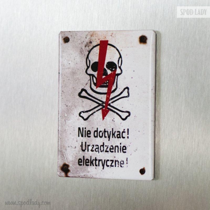 Magnes przypominający tablicę ostrzegawczą: Nie dotykać! Urządzenie elektryczne.